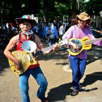 Local act: Broom Duster Kan (left) and a friend step into the sun to play the blues.