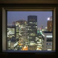 Lighting 'em up: Commercial buildings in Osaka are seen through a window on July 31. Capital spending by Japanese firms rose for the first time in three quarters in the April-June period, the government said Monday. | BLOOMBERG