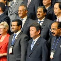 In it together: Trade minister Toshimitsu Motegi (front row, second from right) and other delegates from nations that produce and consume LNG gather in Tokyo on Tuesday. | KYODO