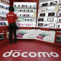 Bid to stop the bleeding: An employee at an NTT DoCoMo Inc. store in Tokyo stands by a display of mobile devices and tablet computers on Tuesday. Japan's largest mobile communications carrier will market the latest iPhones from Sept. 20 to recover market share lost to rivals Softbank Corp. and KDDI Corp. | BLOOMBERG