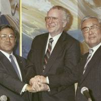 Trans-Pacific cooperation: Toyota Motor Corp. President Shoichiro Toyoda (left), General Motors Corp. Chairman Roger Smith (center) and Toyota Chairman Eiji Toyoda announce the launch of joint venture New United Motor Manufacturing Inc. at a Nagoya hotel in April 1984. | KYODO