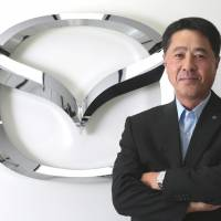 Export-oriented: Masamichi Kogai, president and chief executive officer of Mazda Motor Corp., poses in front of the company's logo in Tokyo last Friday. | BLOOMBERG
