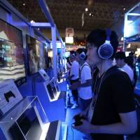 Game on: People try out Sony's PlayStation4 video game consoles at the Tokyo Game Show on Thursday at Makuhari Messe convention hall in Chiba Prefecture. Sony expects sales of the new PS4 to reach 5 million units this fiscal year. | BLOOMBERG