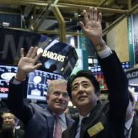 Guest of honor: Prime Minister Shinzo Abe and NYSE CEO Duncan Niederauer wave before Abe rings the closing bell at the New York Stock Exchange on Wednesday. | AP
