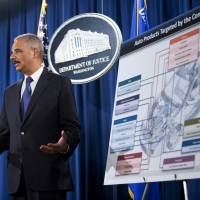 Breaking it down: U.S. Attorney General Eric Holder stands next to a chart illustrating the auto parts case during a news conference at the Justice Department in Washington on Thursday. | AP