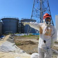 A finger for the dike: Economy, Trade and Industry Minister Toshimitsu Motegi points to tanks filled with radioactive water during an inspection of the Fukushima No. 1 nuclear power plant on Aug. 26. | TEPCO/AFP-JIJI