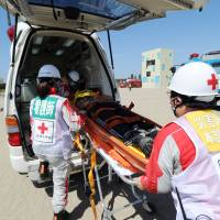 State of readiness: A 'survivor' is placed in an ambulance during a joint disaster response drill held in Chiba on Sunday on the anniversary of the 1923 Great Kanto Earthquake. | AFP-JIJI