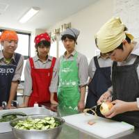 No biting: As other students watch, a member of a cooking club at St. Viator Rakusei Senior High School in Kyoto peels an apple. | KYODO