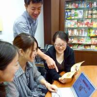 Cooking up a storm: Employees of Ajinomoto Co. in Tokyo on July 10 discuss recipes using leftovers to be introduced on the seasonings maker's website and in brochures. | KYODO