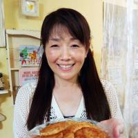 Nothing wasted: Seiko Tabata, a craft artist living in Akishima, Tokyo, shows off pancakes she made from leftover rice.   KYODO