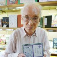 Strong history: Nobuo Okuno holds a set of 'karuta' cards at his long-established store in Tokyo's Kanda-Jimbocho district recently. | KYODO