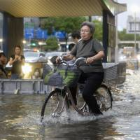 High and wet: A woman bicycles down a flooded street in Naka Ward, Nagoya, around 5:30 p.m. Wednesday as people look on from inside a subway station's flood barrier. | KYODO