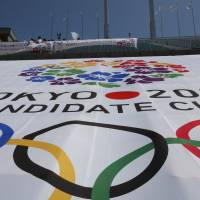 Still burning: The Olympic cauldron, used in the 1964 Tokyo Summer Games, stands above a huge banner bearing the official logo for the capital's bid to host the 2020 Olympics that has been spread over the grandstands at National Stadium. | AP