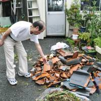 When the wind spins: A man clears roof tiles Thursday in Yaita, Tochigi Prefecture, after a tornado hit the previous day. | KYODO