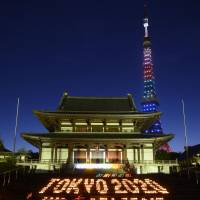 Glowing support: With Tokyo Tower lit up in the background, candles spelling out a positive message to back the capital's 2020 Olympic bid light up an area in front of Zojoji Temple in Minato Ward on Thursday evening. | KYODO