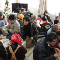 Home from home:  Volunteers from Nagoya offer meals to residents in temporary housing in Ishinomaki, Miyagi Prefecture, on Aug. 31. | AICHI VOLUNTEER CENTER/CHUNICHI SHIMBUN