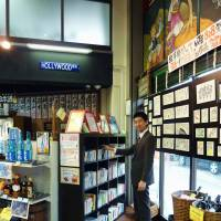 Intoxicating catalog: Naoki Oka, who heads the nonprofit group Joho Station, poses at Sake.come Maehara Library on July 24. The NPO opened a microlibrary inside the liquor store in Funabashi, Chiba Prefecture, in April. | KYODO