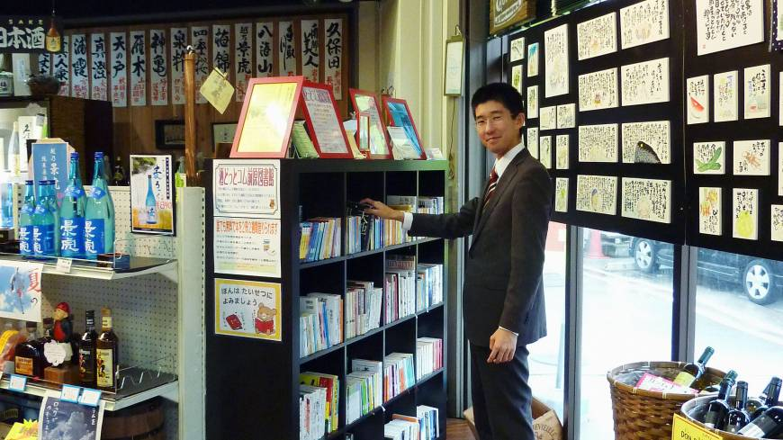 Intoxicating catalog: Naoki Oka, who heads the nonprofit group Joho Station, poses at Sake.come Maehara Library on July 24. The NPO opened a microlibrary inside the liquor store in Funabashi, Chiba Prefecture, in April.