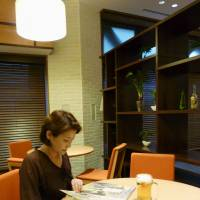 Drinking it in: A woman reads a book over a mug of beer at a restaurant in the Hibiya Library & Museum in Chiyoda Ward, Tokyo, on July 26. | KYODO
