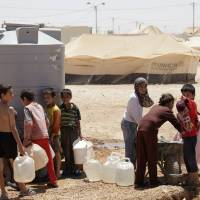Taking stock: Young Syrian refugees refill water jugs at the Zaatari refugee camp in Mafraq, Jordan, near the Syrian border. The site is home to around 120,000 Syrians who fled the more than 2½-year civil war still roiling their country.   AP