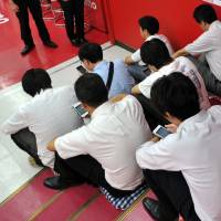 Take a number: People wait at the NTT DoCoMo counter at Bic Camera's Yurakucho outlet in Tokyo to pre-order iPhone 5Cs Friday, a week before the Apple Inc. smartphones go on sale. | YOSHIAKI MIURA
