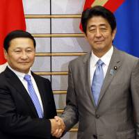 Bridge builders: Mongolian Prime Minister Norov Altankhuyag is greeted by Prime Minister Shinzo Abe shakes prior to their meeting in Tokyo on Friday. The two leaders signed an agreement to strengthen the Mongolia-Japan strategic partnership. | AFP-JIJI