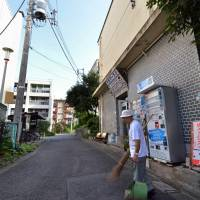 Booted out again: Kohei Jinno, 79, who has been asked to move to make way for the expansion of National Stadium in Tokyo for the 2020 Olympic Games, sweeps the road in front of his apartment complex in Kasumigaoka on Saturday. | AFP-JIJI
