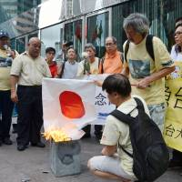 Memories fresh: Protesters burn a Hinomaru flag during an anti-Japanese rally in Hong Kong on Aug. 15 to mark the anniversary of Japan's surrender in World War II in 1945. On Sunday, turnout was small for a protest march held to condemn Japan's effective nationalization last year of the disputed Senkaku Islands. | KYODO