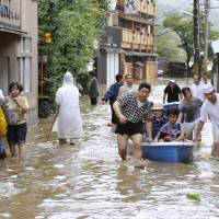 A makeshift rescue boat carries inn guests to safety in Kyoto's Nishikyo Ward Monday morning.    KYODO