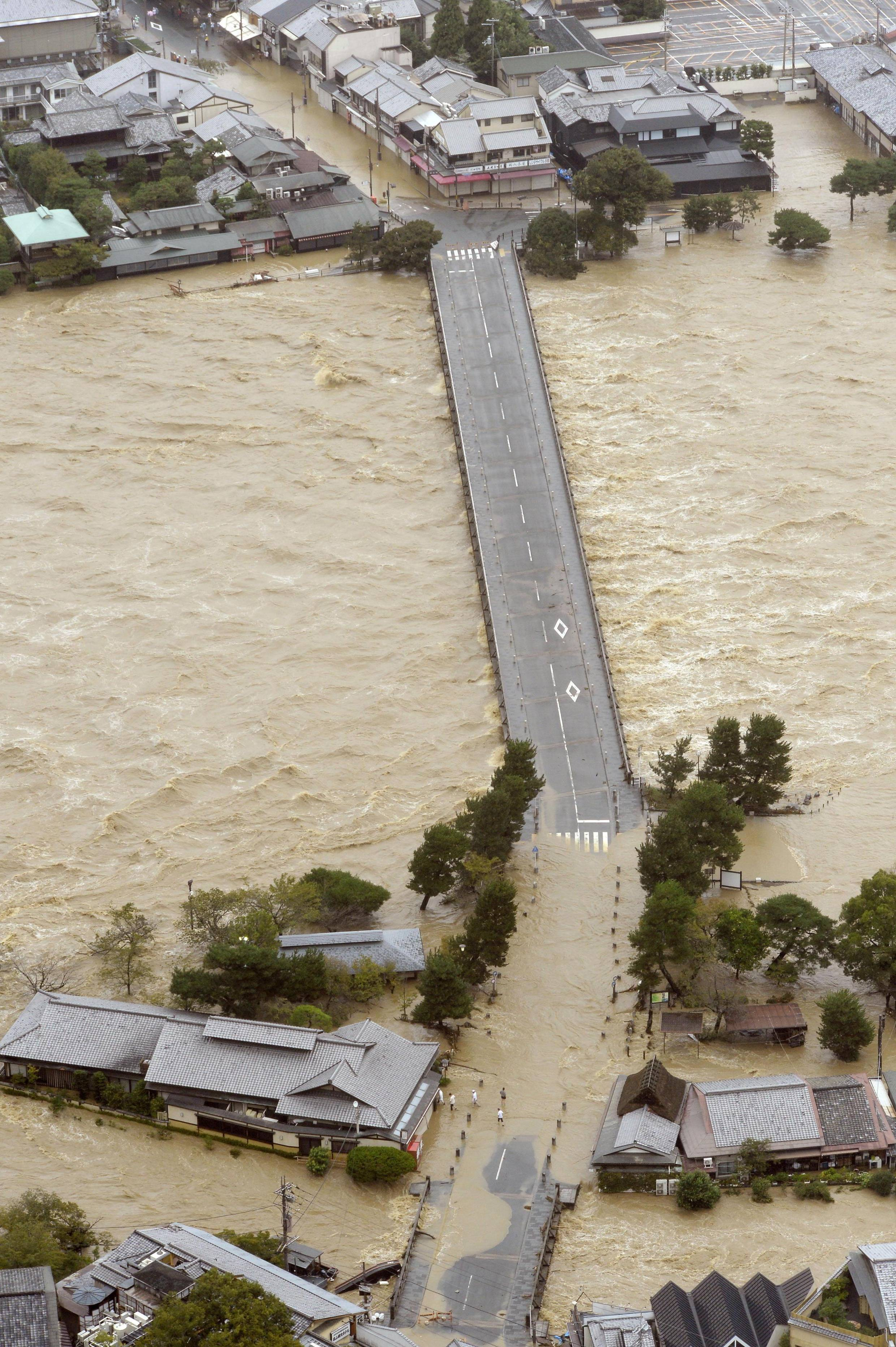 An aerial photo shows floodwaters washing out a bridge that spans Katsurugawa River in Kyoto.