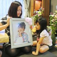 Not forgotten: Mika Sato holds a picture of her daughter Airi, who died in the March 11, 2011, tsunami, as her younger daughter Juri looks on in their home in Ishinomaki, Miyagi Prefecture, on Aug. 22. | KYODO