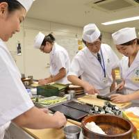 Roll with it: Women practice making sushi rolls under the guidance of a Tokyo Sushi Academy chef on July 23. | KYODO