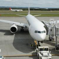 Smoking landing: A JAL Boeing 777 that appeared to be emitting smoke from its landing gear taxies at New Chitose Airport, near Sapporo, on Thursday. | KYODO