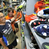 Good fit: Yoshihito Nakayama, locker room staffer for Shimizu S-Pulse, holds a pair of shoes in the clubhouse of the professional soccer club in Shizuoka. | KYODO