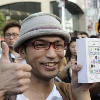 Top of the line: The first customer who purchased the iPhone 5S at the company's flagship store in Ginza gives a big thumbs up. | Bloomberg