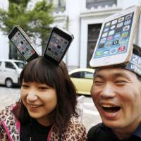 A step ahead: Yui Kashima, left, and Nobuhiko Matsuda, sport handmade iPhone headgear as they wait in line Friday to buy Apple's new iPhone 5 outside a store in Tokyo. | AP