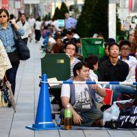 Wait for it: A kimono-clad woman passes people queuing for new Iphones in Ginza on Thursday.