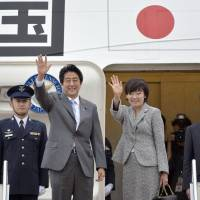Right on cue: Prime Minister Shinzo Abe and his wife, Akie, leave Tokyo Monday to hold talks in Canada and attend the U.N. General Assembly meeting in New York. | KYODO
