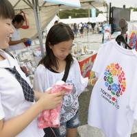 Cashing in: Two sisters look at a T-shirt emblazoned with the bid emblem for the Tokyo 2020 Olympics at an event in Tokyo's Komazawa Olympic Park. Several industries are waiting for big opportunities to emerge from the sporting extravaganza. | KYODO
