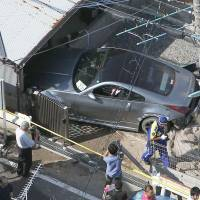 Inexperienced driver: A Nissan Fairlady Z is seen slammed into a garage after it plowed into a group of five elementary school children Tuesday morning in Yawata, Kyoto Prefecture. The driver, an 18-year-old male, reportedly told police he was going too fast around a bend.   KYODO
