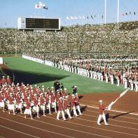 Big step: Japanese athletes walk during the opening ceremony for the 1964 Tokyo Olympics at the national stadium on Oct. 10, 1964. | KYODO