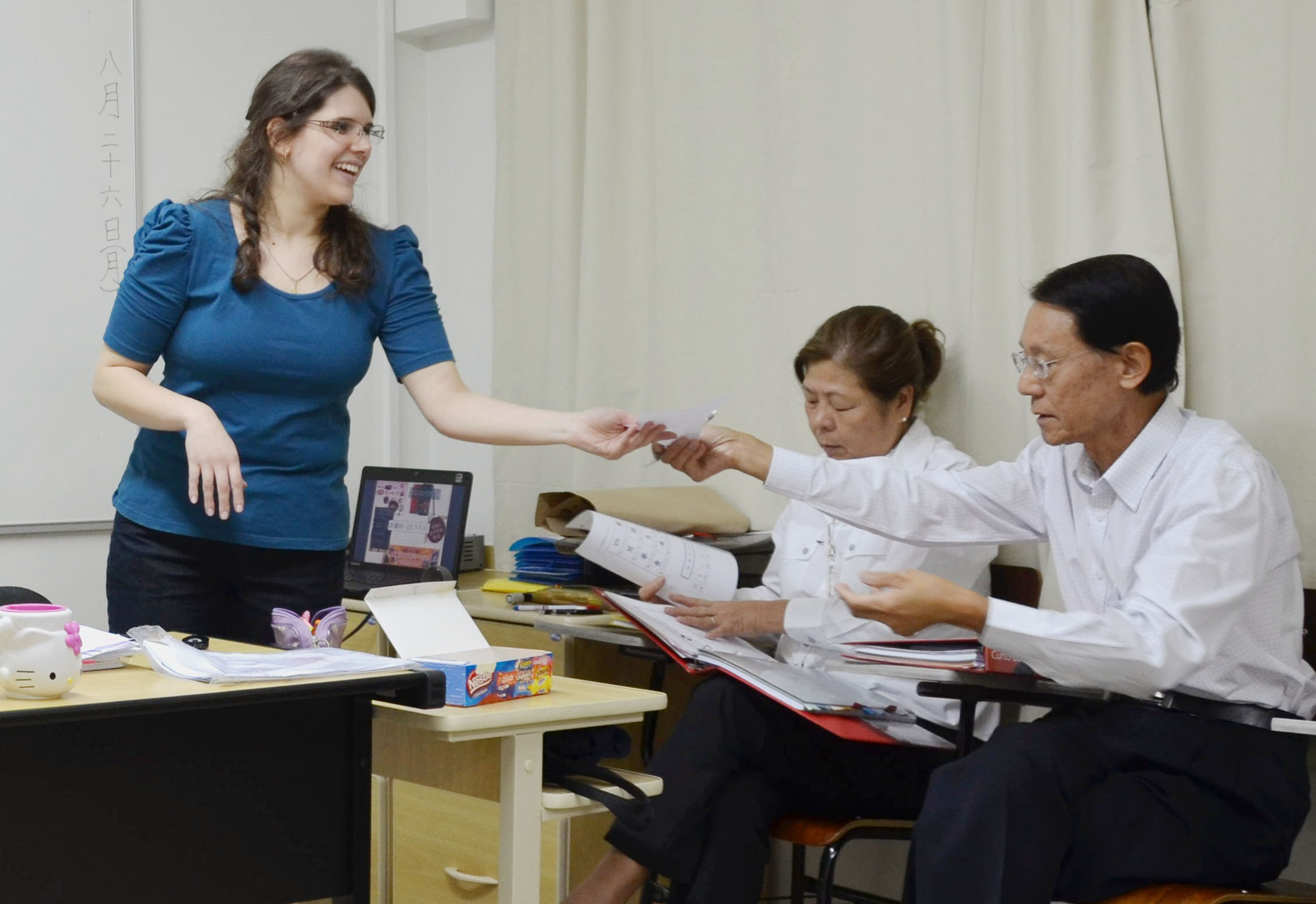 Filling the gap: Japanese-Brazilian students hand in a homework assignment to teacher Aline Wanderley at a Japanese-language school in Sao Paulo recently. | KYODO
