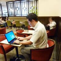 Power-hungry: A customer works on a laptop plugged into an outlet at a Renoir coffee shop in Shinjuku Ward, Tokyo.   KYODO