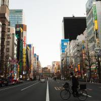 Bike this way: A man on a bicycle crosses a street in Tokyo's Akihabara district. The police are warning cyclists to stick to the left side of the road from now or face jail time and other penalties under a recent revision to the traffic law. | BLOOMBERG