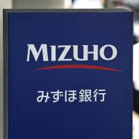 Criminals' bank of choice: Pedestrians walk by a sign for Mizuho Bank in Tokyo. Financial regulators on Friday ordered the mega-bank to stop lending money to yakuza. | BLOOMBERG