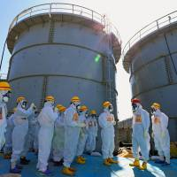 Prime Minister Shinzo Abe (third from right) inspects a site Thursday near a storage tank that recently sprung a leak of radioactive water at the Fukushima No. 1 power plant. | KYODO