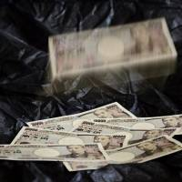 Now you see it, . . .: A pile of ¥10,000 bank notes appears to be disappearing into thin air as the National Police Agency warns that cyberthieves have plundered Japan's Internet banking accounts to the tune of ¥550 million so far this year. | BLOOMBERG