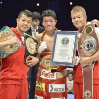 Daiki Kameda (center) poses with brothers Koki (left) and  Tomoki after beating Rodrigo Guerrero on  Tuesday to win the IBF super-flyweight title. The Kamedas are the first trio of brothers to hold world titles at the same time.   | KYODO