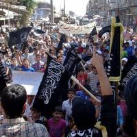 Sectarian slide: Anti-Syrian regime protesters hold al-Qaida flags with Arabic writing that reads, 'There is no God but Allah and Mohammed is his messenger,' as they chant slogans during a demonstration in Aleppo, northern Syria, on Friday.  | AP
