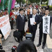 Righting a wrong: Lawyers for plaintiffs seeking equal inheritance rights for offspring born out of wedlock rejoice Wednesday outside the Supreme Court after the court ruled against the existing legal discrimination against their clients, with one attorney holding up a banner reading the verdict: 'unconstitutional.'  | KYODO